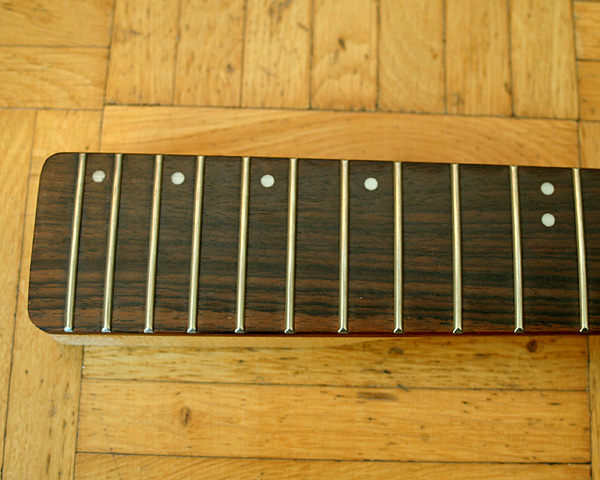 The no-name neck has little dots on the upper edge, I am thinking to remove these and fill the holes with brown wood filler so that you have some help with finding the right fret without changing the look of a board without dot markers.